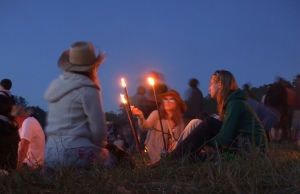 A group sits around candles at Glastonbury
